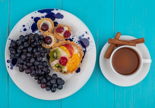 Vista dall'alto di cupcakes fruttati e uva nel piatto e tazza di tè con cannella sul piattino su sfondo blu
