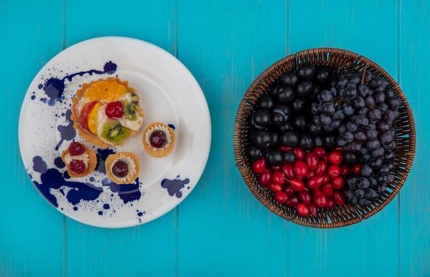 Vista dall'alto di cupcakes fruttati nel piatto e frutta come prugnole di corniolo bacche e uva su sfondo blu