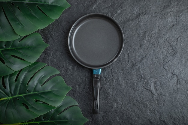 Top view of frying pan over black background with green leaves.