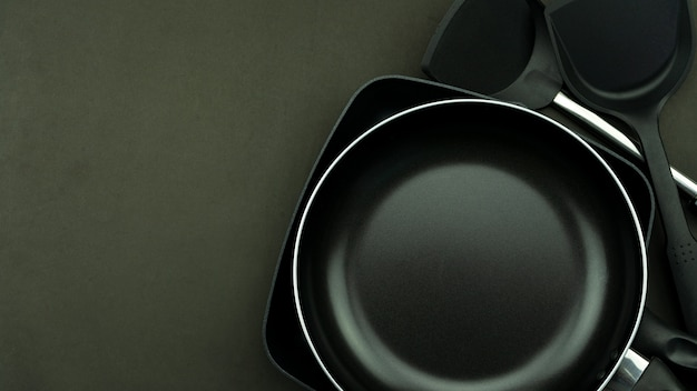 Top view frying pan and pot on black background.