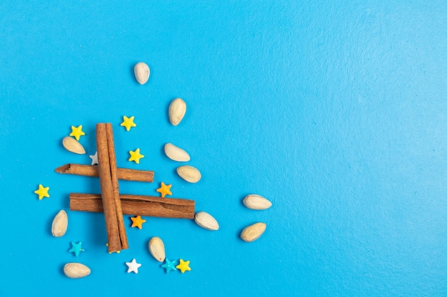 Top view ful sweet candies star shaped with cinnamon on the blue background