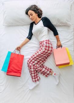 ショッピングバッグとクレジットカードを手にカジュアルな服を着た美しい若い巻き毛のブルネットの女性のフルレングスの写真。ショッピングモールでの買い物を夢見ています。ブラックフライデー