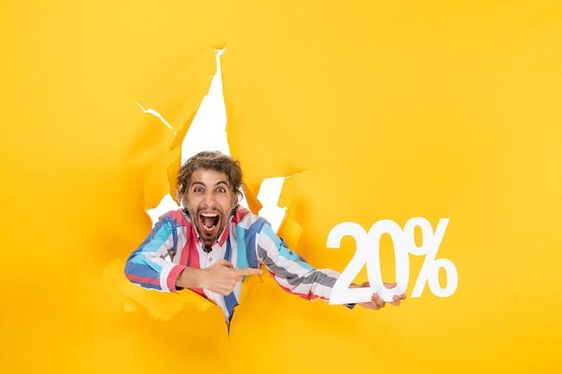 Vista dall'alto di un giovane divertente che tiene una ventina di percentuale in un buco strappato in carta gialla