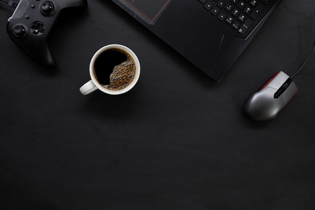 Top view of gamer desk workspace with coffee cup and laptop on black table
