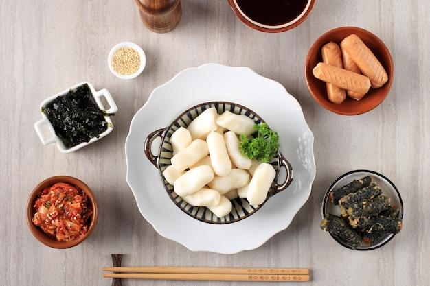 Вид сверху корейский рисовый пирог garaetteok (палочка из закругленного рисового торта) с сыром моцарелла внутри. сырые ингредиенты для изготовления ттеокбокки, традиционной корейской кухни.