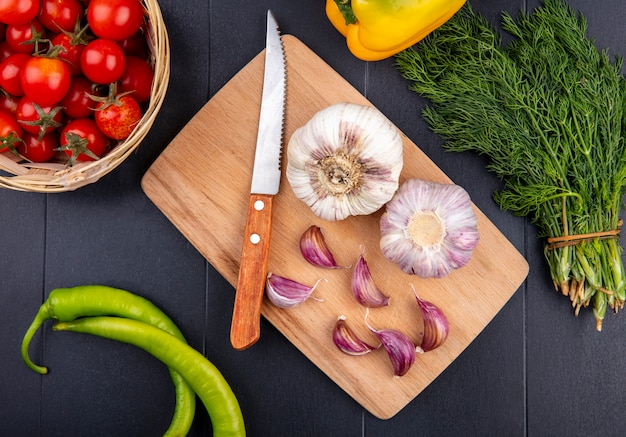 Top view of garlic bulb and cloves with knife on cutting board and basket of tomato on black surface