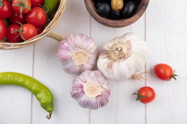 Vista dall'alto di bulbi di aglio con olive, pepe e pomodorini su superficie di legno