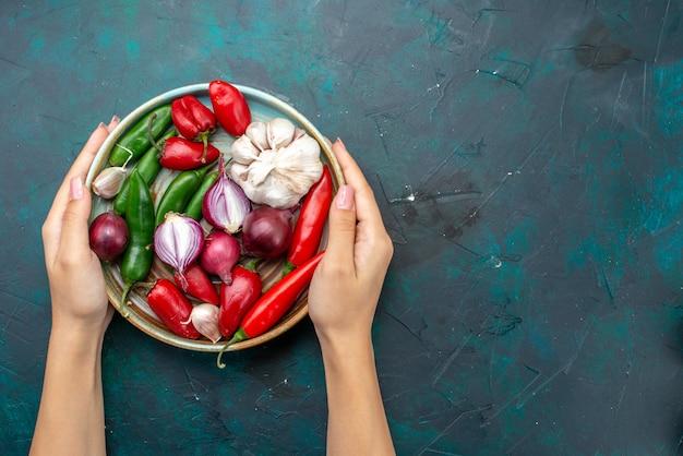 Vista dall'alto di garlics e cipolle con peperoni rossi sulla scrivania scura, insalata di farina di cibo vegetale