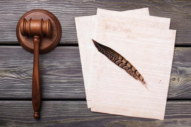 羽ペンと紙で上面図のガベル。灰色の机の背景。