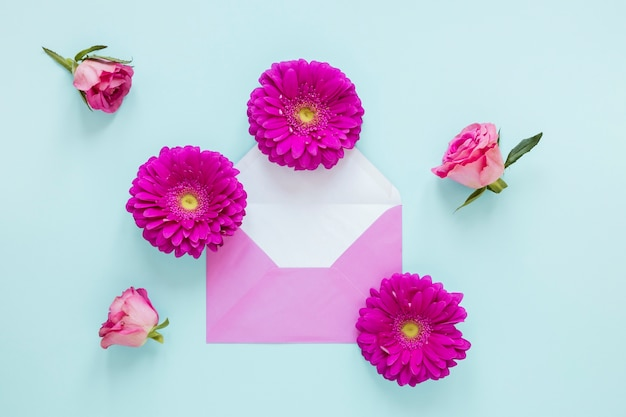 Top view gerbera and rose flowers and envelope