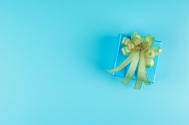 Top view of gift box on blue color with golden ribbon and copyspace