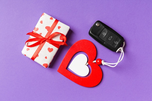Top view of gift box, car key and wooden heart
