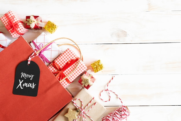 Top view of gift box and red shopping bag with message tag on a wooden white background.