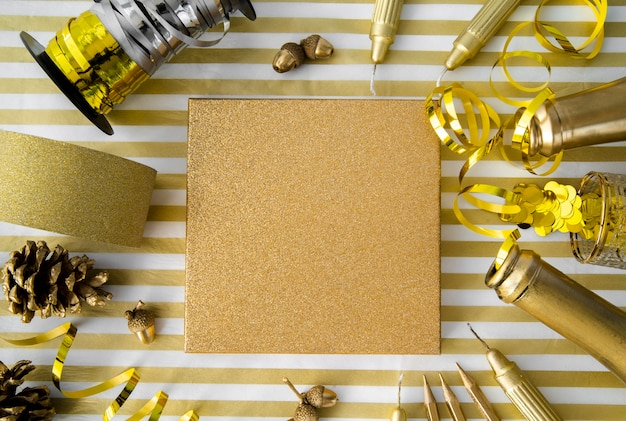 Top view gift box surrounded by golden ribbons and sequins