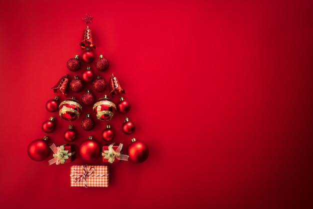 Top view of gift box with red ball and bell in shape of christmas tree on red background.