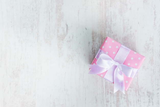 Top view of a gift box wrapped in pink dotted paper and tied satin bow over white wood.