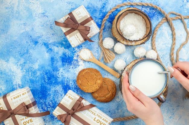 Vista dall'alto scatole regalo palline di cocco corda biscotti tazza di latte in mano femminile su sfondo bianco blu