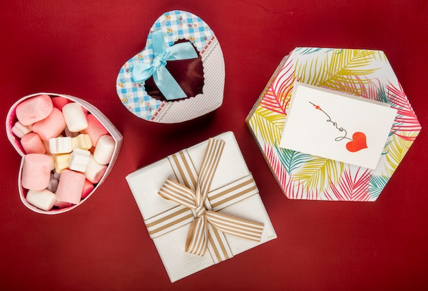 Top view of gift boxes of different shapes and colors and marshmallow in a heart shaped box on red table