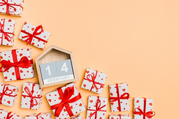 Top view of gift boxes with red hearts and wooden calendar