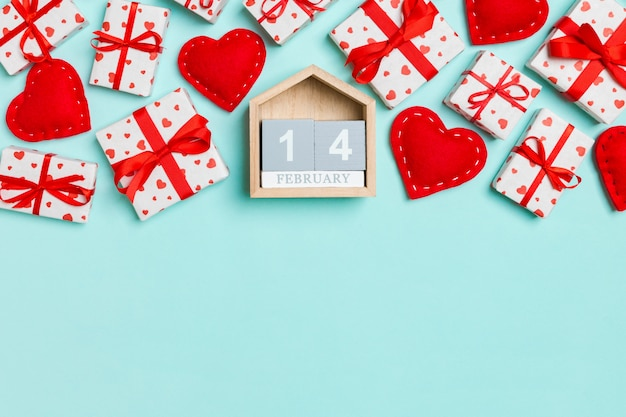 Top view of gift boxes, wooden calendar and red textile hearts