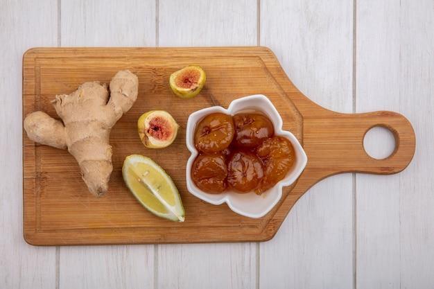 Vista dall'alto lo zenzero con fetta di limone e marmellata di fichi in un piattino su un tagliere su sfondo bianco