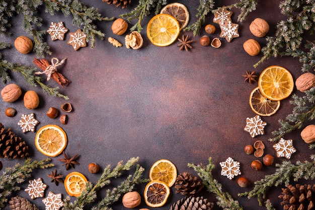 Top view of gingerbread cookies with pine cones and dried citrus frame