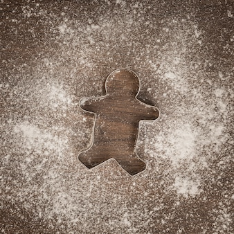 Top view gingerbread man cookie cutter with flour