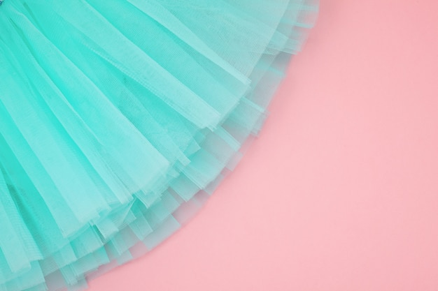 Top view over the girl ballet tutu dress over the pink background