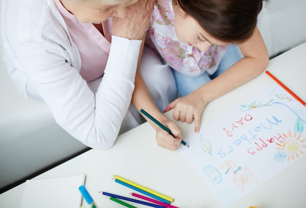 Top view of girl drawing with her grandmother