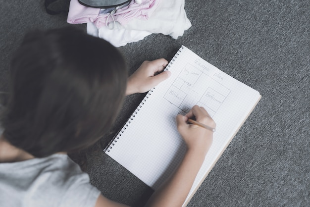 Top view of girl draws in notepad lying on floor
