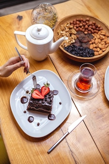 Top view girl eats chocolate cake with a cup of tea and nuts