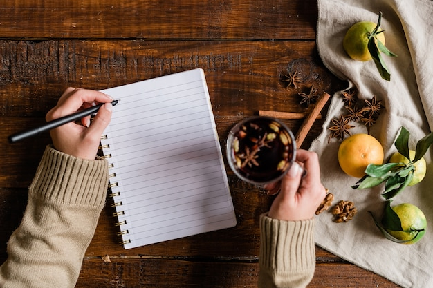 Top view of girl hands holding glass of mulled wine and pen over blank page of notebook while sitting by wooden table