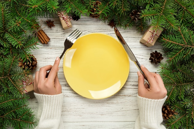 Top view girl holds fork and knife in hand and is ready to eat. empty plate round ceramic on wooden christmas background.
