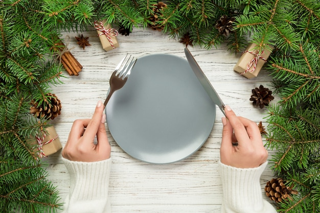 Top view girl holds fork and knife in hand and is ready to eat. empty plate round ceramic on wooden table. holiday dinner dish concept with christmas decor
