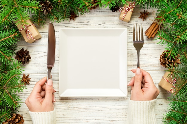 Top view girl holds fork and knife in hand and is ready to eat. empty white square plate on wooden christmas background. holiday dinner dish  with new year decor