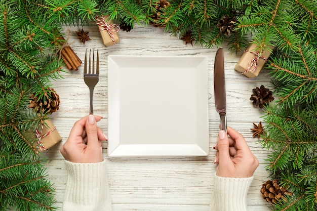 Top view girl holds fork and knife in hand and is ready to eat. empty white square plate on wooden christmas decoration