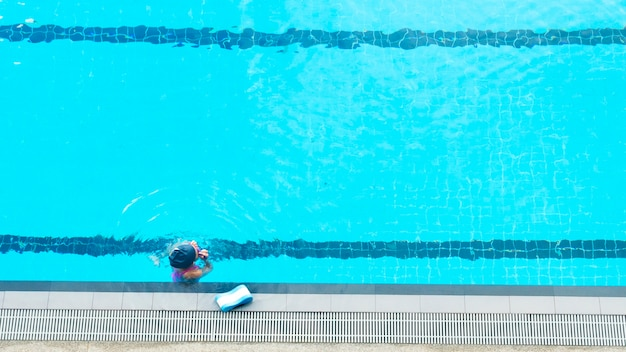 Top view of girl kid in the water swimming pool