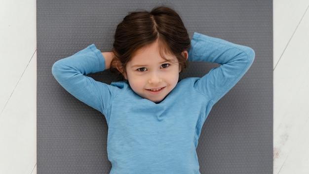 マットの上に横たわっている上面図の女の子