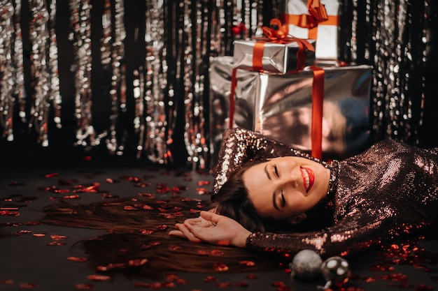 Top view of a girl lying in shiny clothes on the floor in confetti in the form of hearts and gifts.