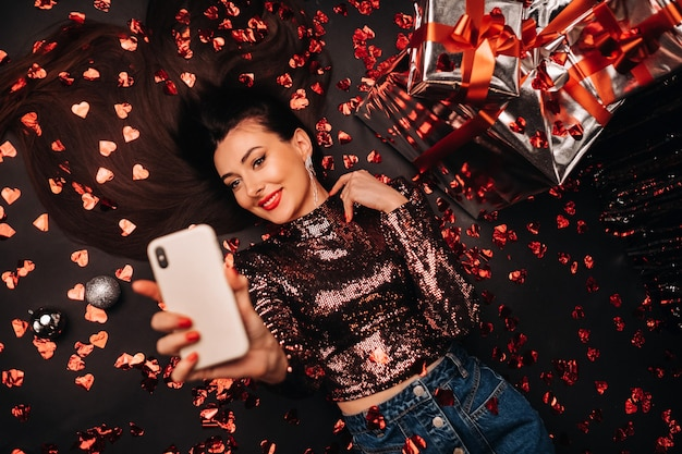 Top view of a girl lying in shiny clothes on the floor in confetti in the form of hearts and taking a selfie.