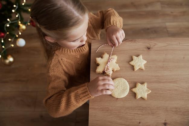 Vista dall'alto della ragazza che imballa i biscotti per babbo natale