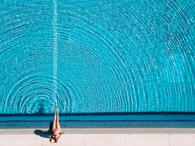 Top view of girl relaxing next to pool