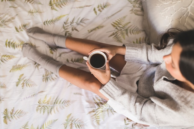 Top view of a girl sitting on bed holding cup of coffee
