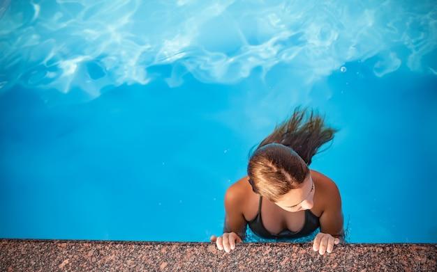 상위 뷰 소녀 십대는 따뜻한 맑고 푸른 물에 수영장에서 수영