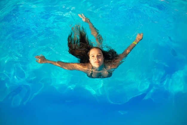 Top view girl teenager swims in the pool in warm clear blue water on sunny summer