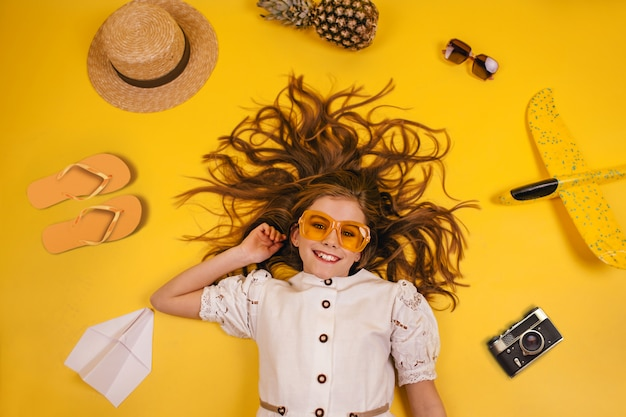 Top view of a girl who travels, collection of leisure items on a yellow background