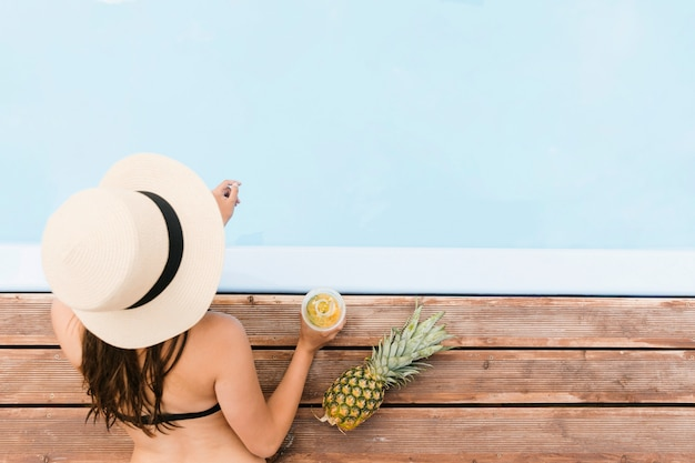 Top view girl with pineapple nearby pool