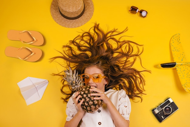 Top view of a girl with a pineapple who travels, collection of leisure items on a yellow background