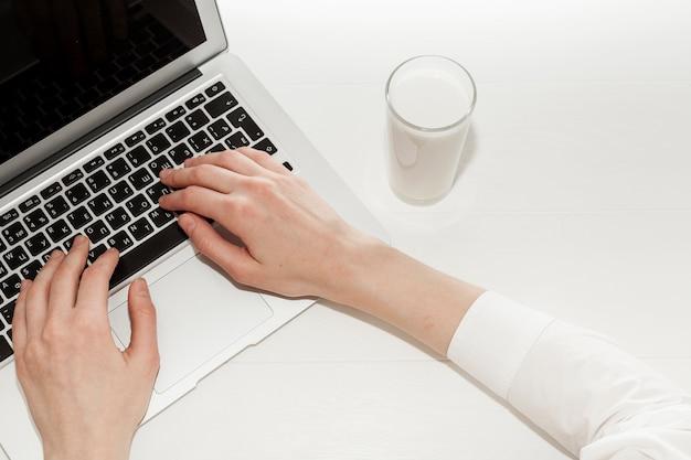 Ragazza di vista superiore che lavora al suo computer portatile accanto a un bicchiere di latte