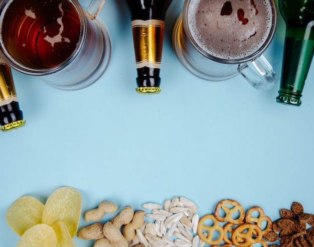 Top view of glass of beer and a bottle with mix of salty snacks on blue with copy space